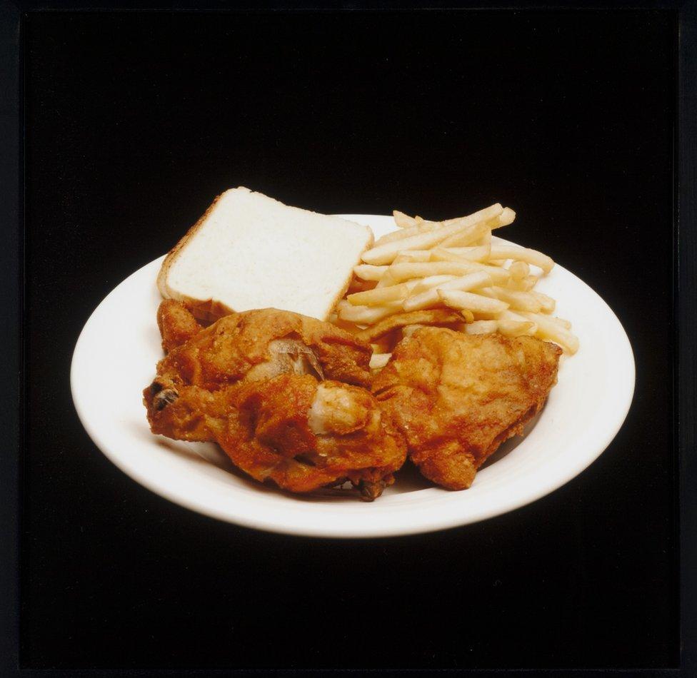 Papas fritas, pollo frito y una tajada de pan blanco.