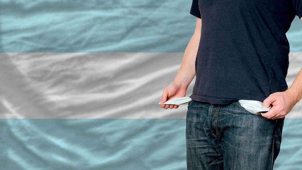 Un hombre muestra sus bolsillos vacíos, frente a una bandera de Argentina