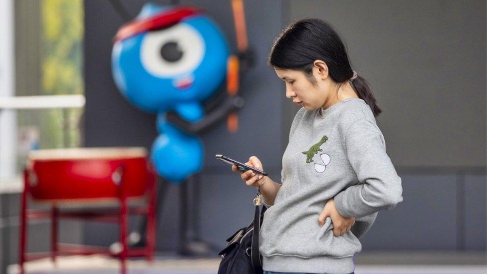 Una mujer, junto a la mascota del Grupo Hormiga.