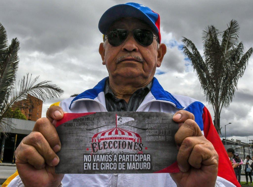 """Hombre con cartel que dice: """"No vamos a participar en el circo de Maduro"""""""