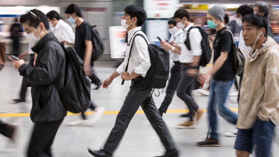 pessoas caminhando na rua de máscara