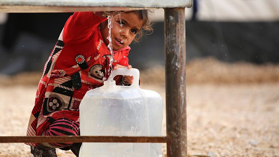 A girl getting water from a tank