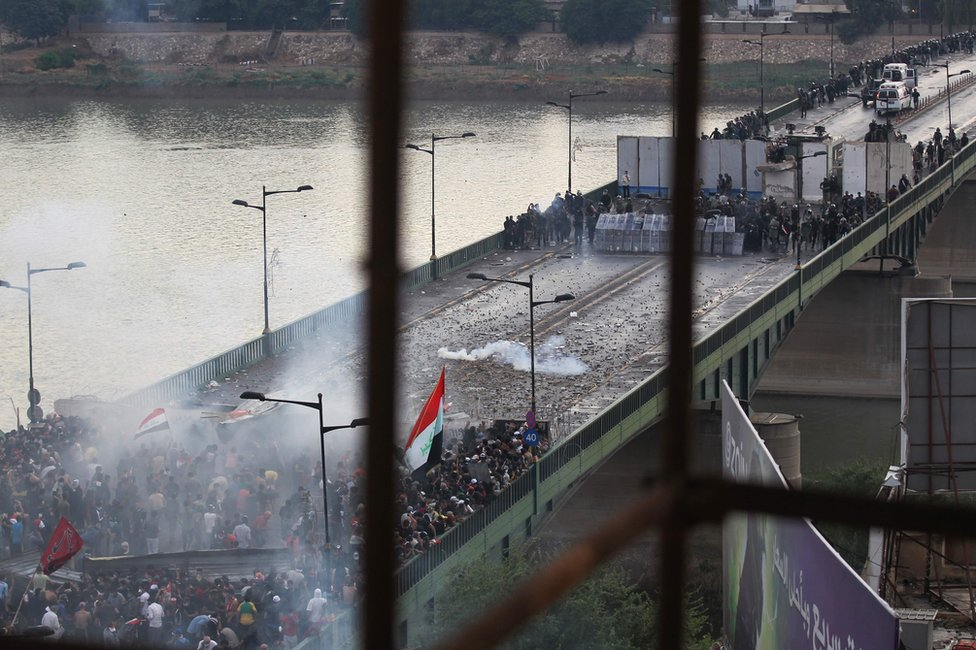Iraqi security forces fire tear gas to stop protesters attempting to cross al-Jumhuriya bridge from Tahrir Square, Baghdad (25 October 2019)