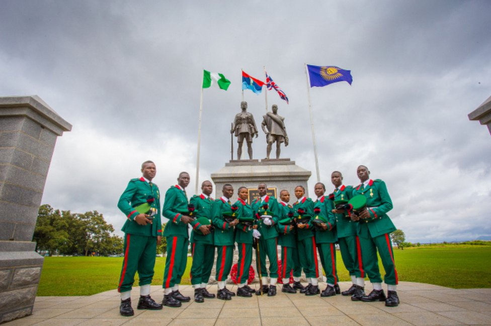 Male and female soldiers in green and red uniforms stand in front of the memorial featuring flags and two statues in Abuja