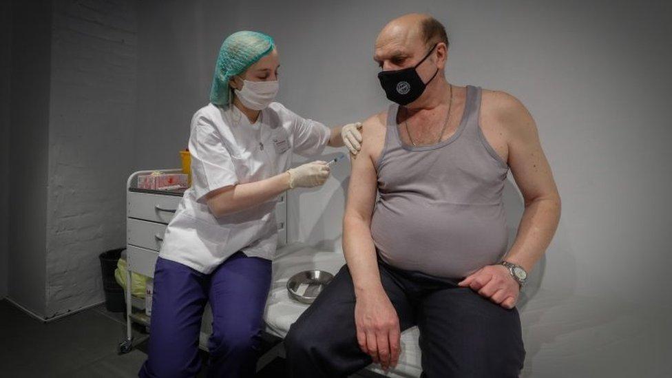 Enfermeira aplica vacina em homem russo