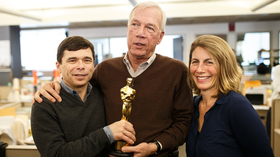 The Boston Globe's Michael Rezendes, left, Walter V. Robinson, and Sacha Pfeiffer, right, hold Oscar winning writer Josh Singer's Oscar statue in the newsroom of the Boston Globe