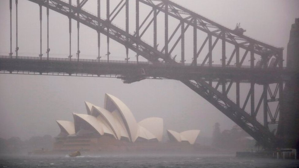 Storms clouds are seen behind the Sydney Opera House and Sydney Harbour Bridge