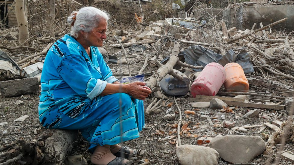Woman sits amid the rubble of a bulding