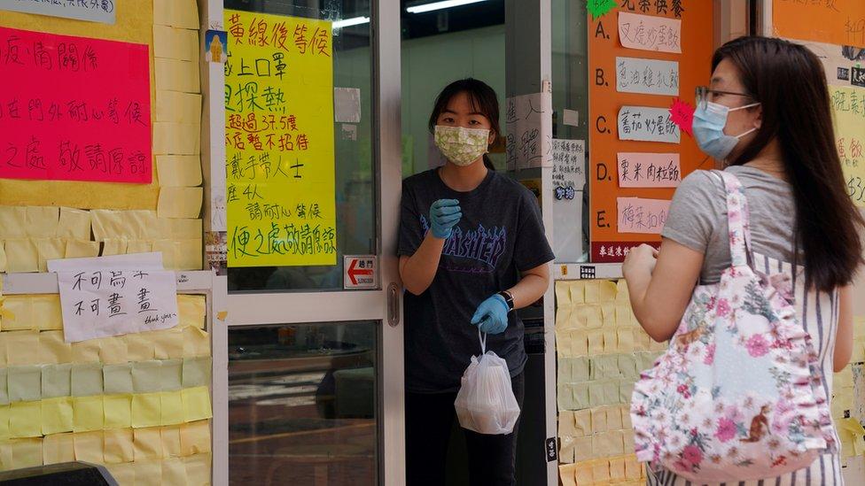 Funcionária usa máscara facial após o surto de covid-19 e entrega comida para um cliente em frente a um restaurante em Hong Kong