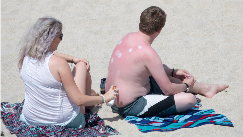A woman applies sun lotion to a man's back as they enjoy the fine weather on Porthmeor Beach in St Ives