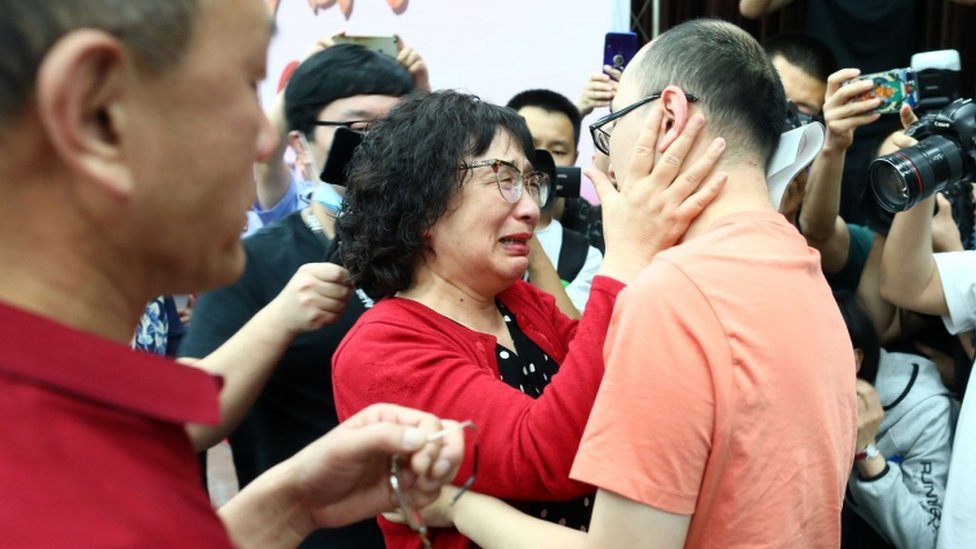 Li Jingzhi llora y abraza a su hijo.