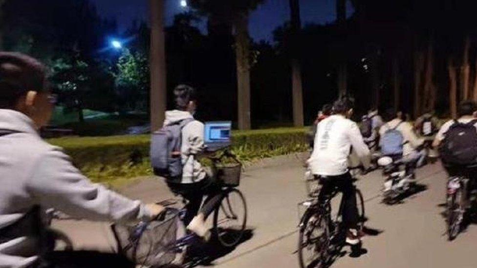 Un estudiante de la Universidad Tsinghua opera su computador portátil mientras monta en bicicleta.