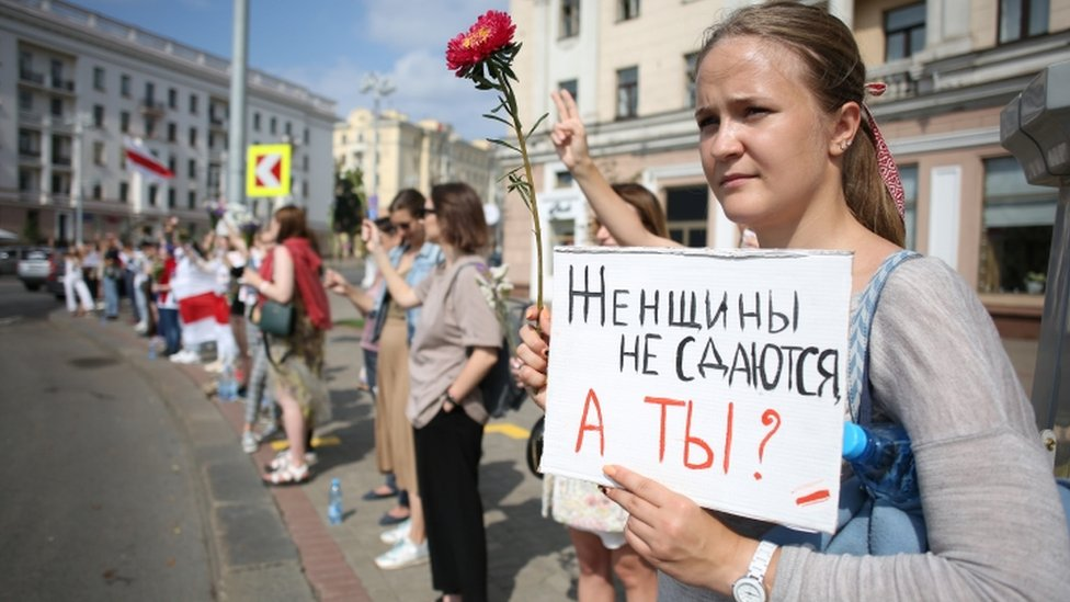 "Protester in Minsk holds up sign saying: ""Women don't surrender, and you?"""