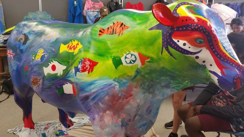 A colourful bull statue that has country flags in the shape of fish painted on it