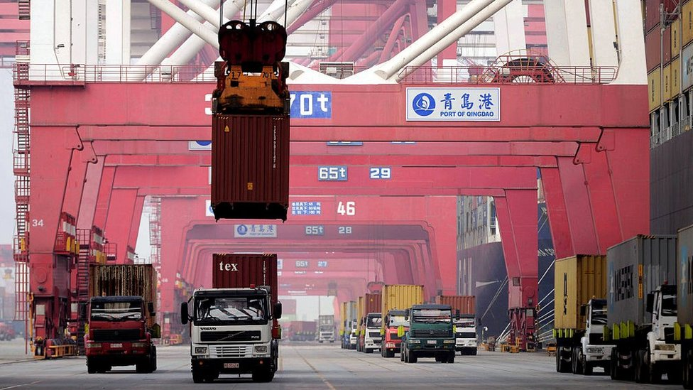 A container is lifted by a crane at a port in Qingdao, east China's Shandong province