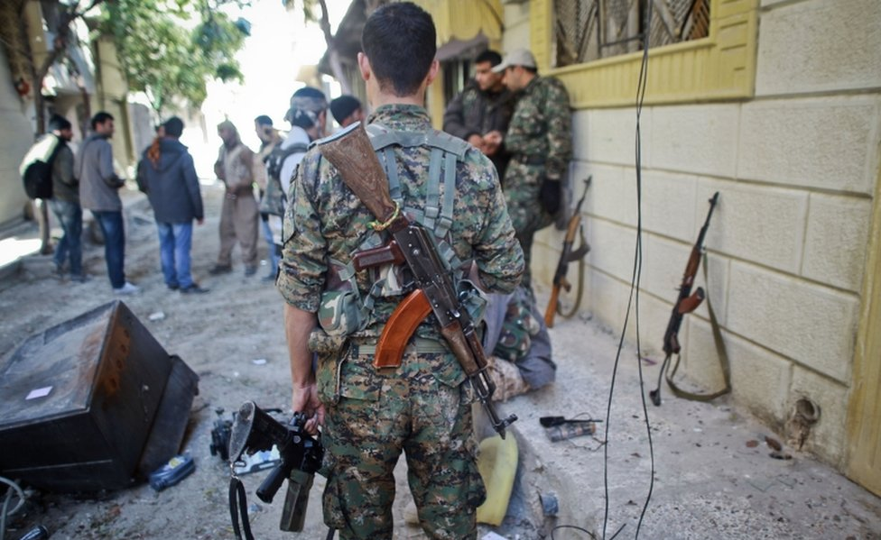 YPG fighters pictured on the street in a besieged Syrian border town in November 2014