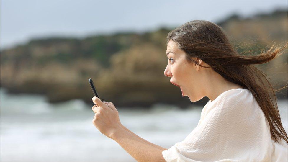 Mujer mirando un celular.