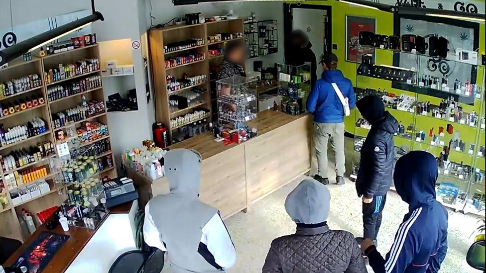 CCTV footage show six alleged armed thieves talking with the shop owner