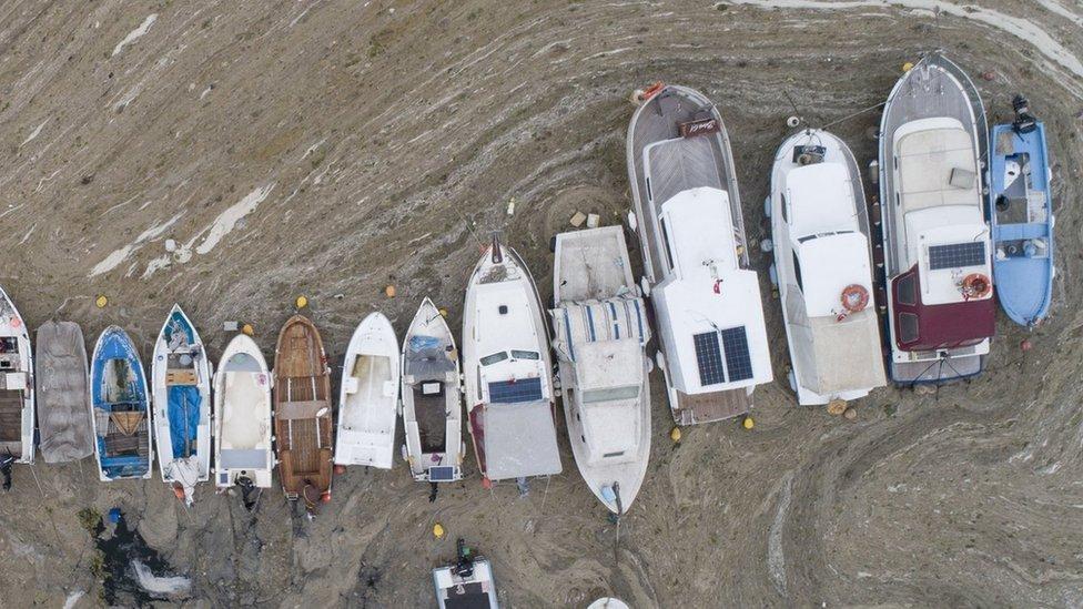 """Pequeños barcos de pesca cubiertos por eld """"moco de mar""""."""