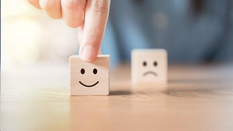 Un cubito de madera con una cara feliz y otro con una cara triste