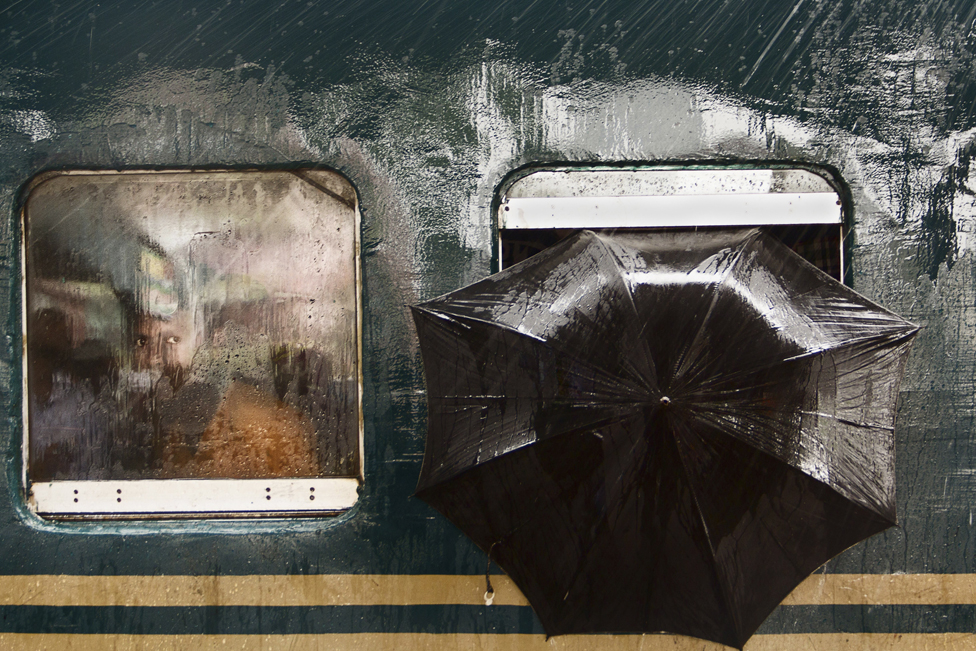A man looks out from a train at Tongi Railway Station, Gazipur, Bangladesh
