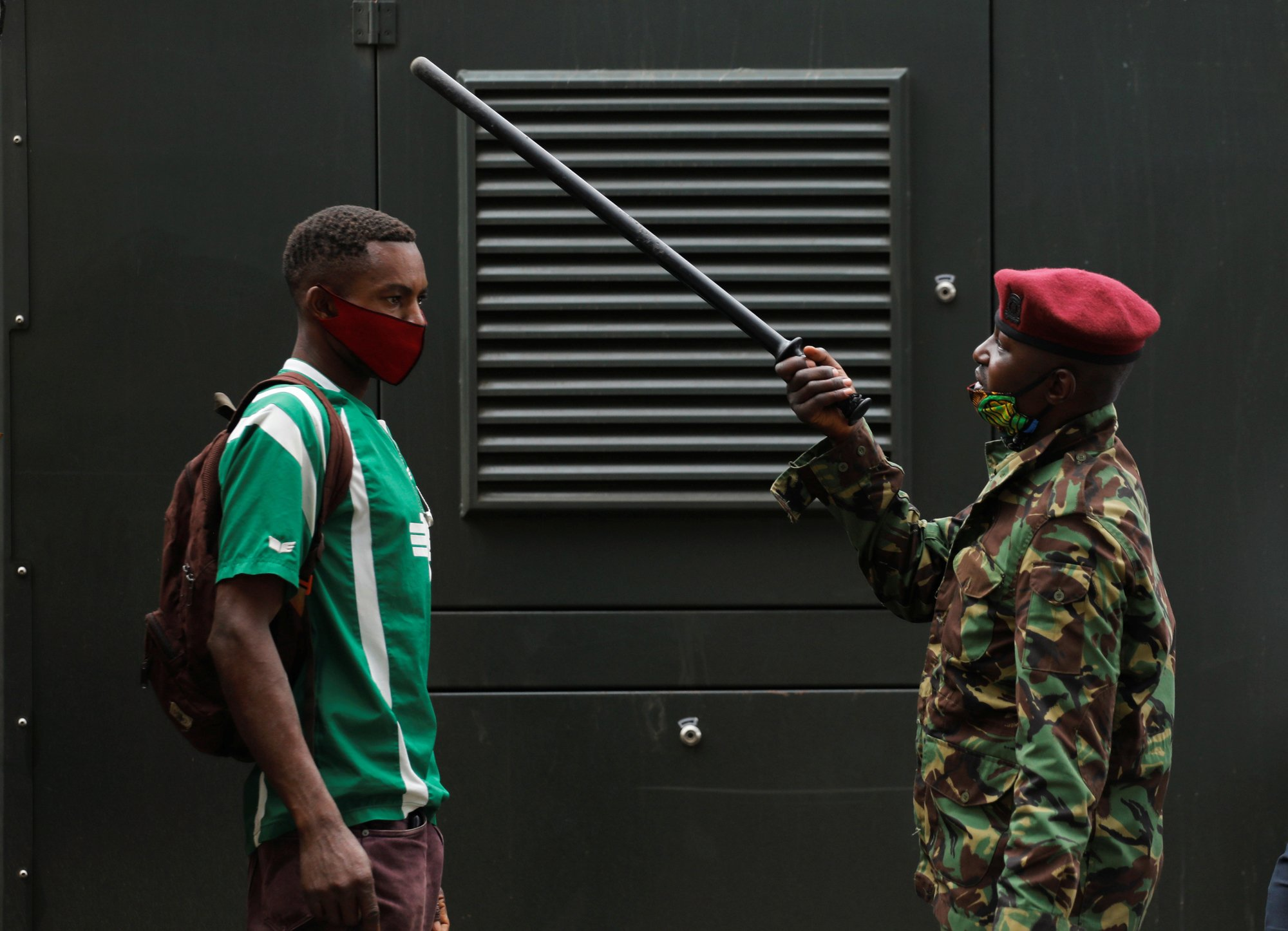 Un policía cuestiona a un transeúnte en un retén de control contra coronavirus en Kenia