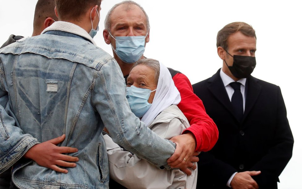 French President Emmanuel Macron (R) stands next to French aid worker Sophie Petronin (C) who is welcomed by her family after suspected jihadist hostage-takers freed the 75-year-old from nearly four years of captivity in Mali upon her arrival at the Villacoublay military airport near Paris on October 9, 2020.