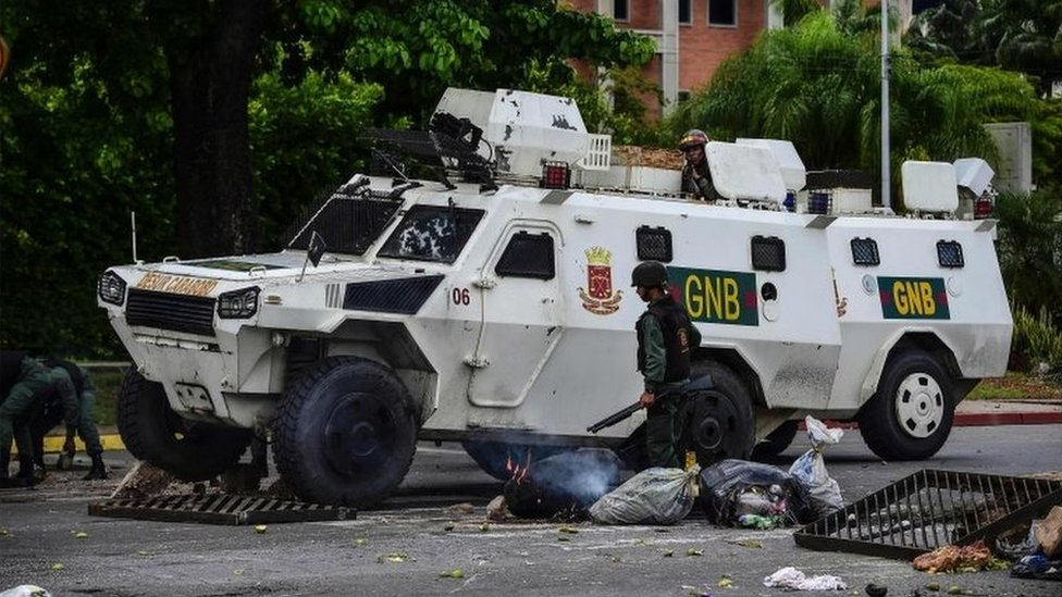 A National Guard vehicle goes through a barricade built by anti-government activists in Venezuela's third city, Valencia, on August 6, 2016,