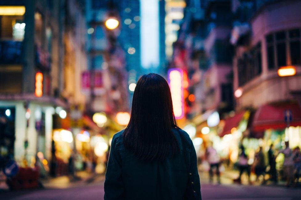 Mujer de espaldas en una ciudad.
