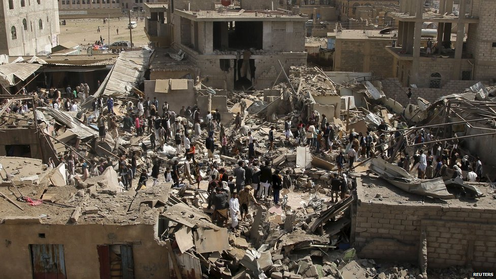 People and vendors gather on the rubble of shops destroyed by a Saudi-led air strike that hit a marketplace in Yemen's capital on 20 July, 2015