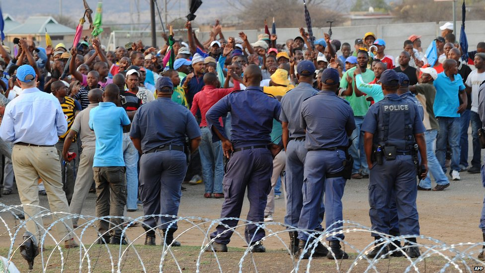 Police stand by as striking miners celebrate securing a 22% pay hike from London-listed Lonmin platinum mine in Marikana on September 18, 2012.