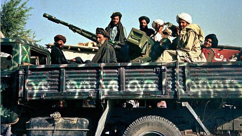 Los soldados talibanes afganos el 28 de julio de 2000 posan en Kabul en su camión militar recién pintado con su arma antiaérea de camino hacia el norte de la capital.
