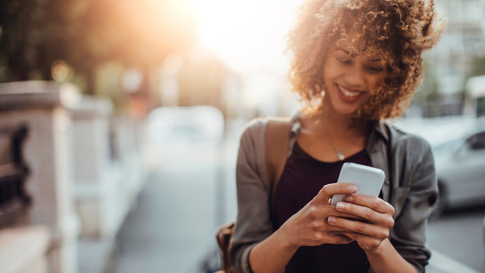 Stock image of women using a mobile phone in the street