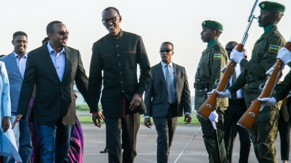 Paul Kagame (C) welcomes Ethiopia's PM Abiy Ahmed to the memorial events
