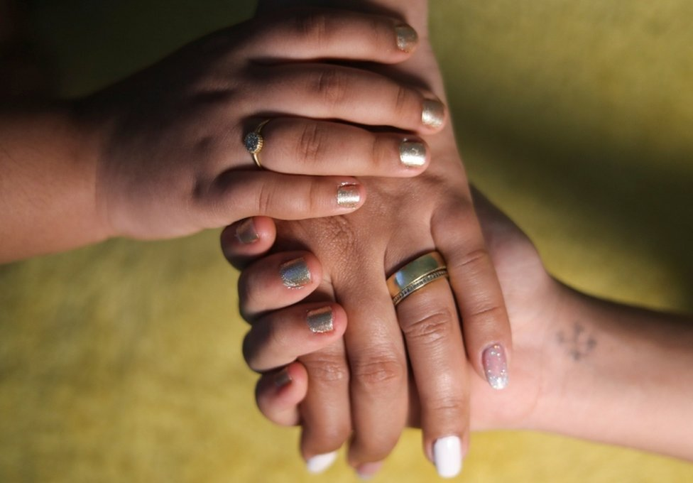 A close shot of a woman holding hands with her two young daughters.