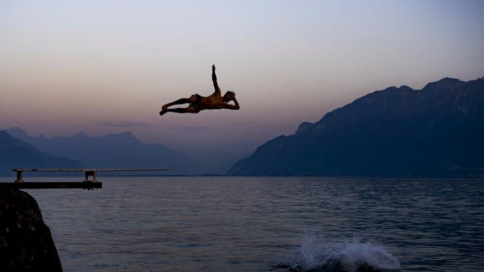 People cool down at sunset in Lake Geneva - 26 June