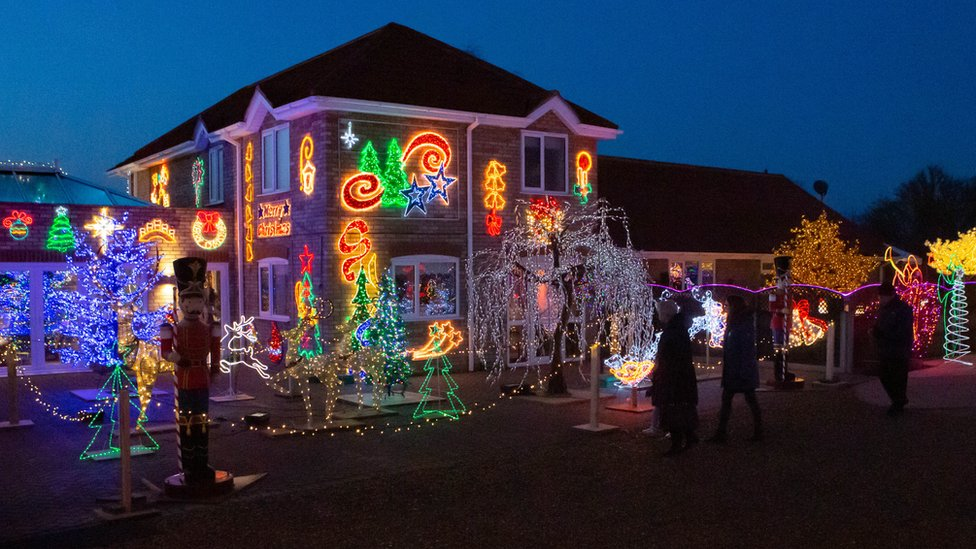 The outside of a house heavily decorated with Christmas lights.