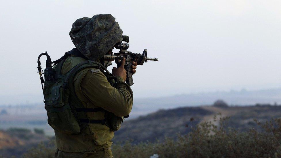 Un soldado israelí apunta con su arma en las cercanías de la frontera de Gaza.