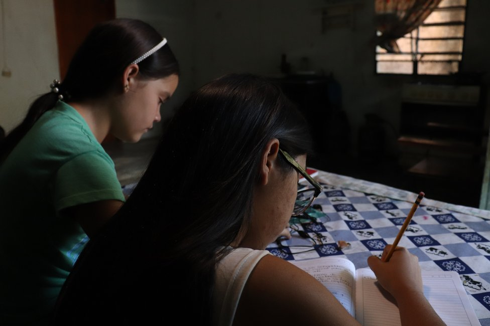 Valeria Torres writing on a notebook, with a student next to her