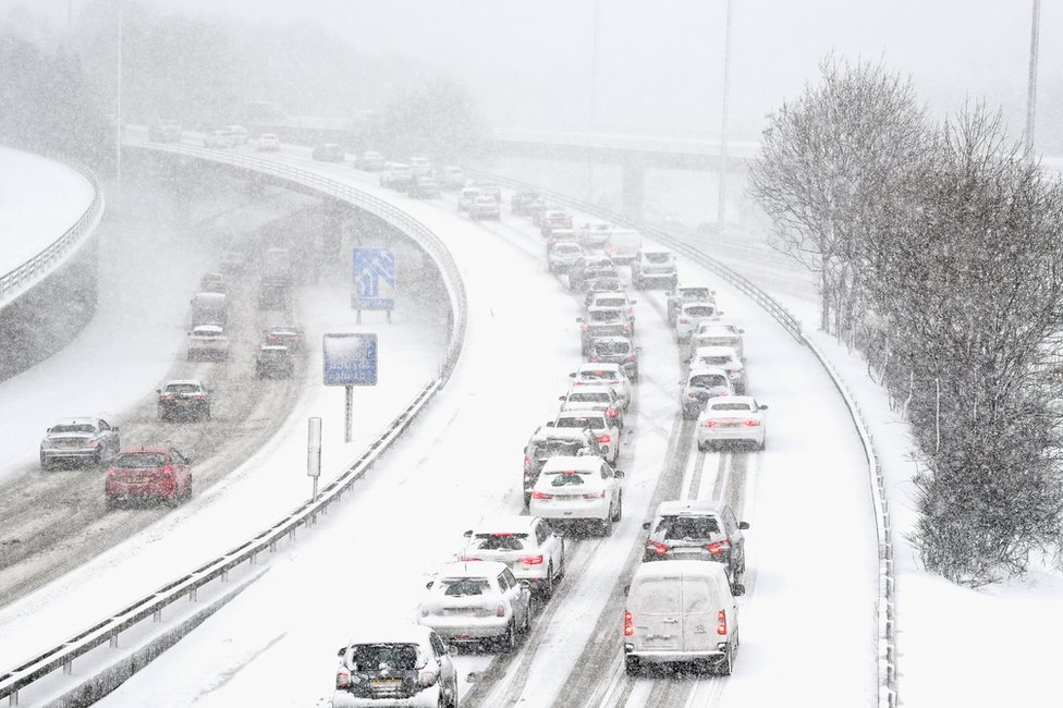 Vehicles drive through snow on the M8 in Glasgow