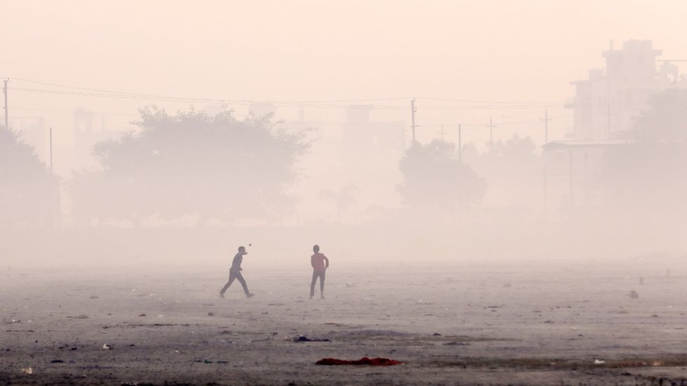 Children playing cricket in smog