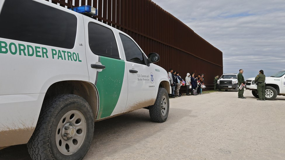 Families that crossed the border to enter the US illegally turn themselves in to US Border Patrol agents next to a fence along the Rio Grande River near McAllen, Texas, 23 January 2019