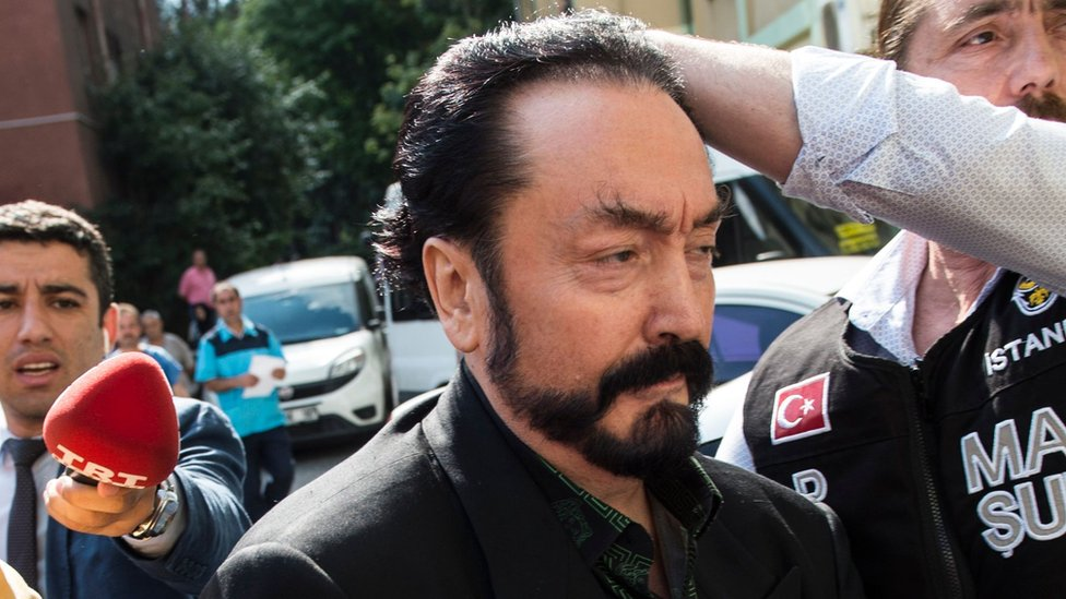Turkish police officers escort televangelist and leader of a sect, Adnan Oktar (C) on July 11, 2018, in Istanbul, as he is detained on fraud charges.