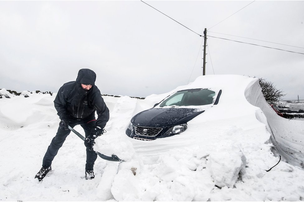 A person digging their car out from under heavy snow