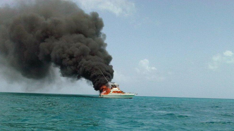 A boat on fire off the shore of Antigua