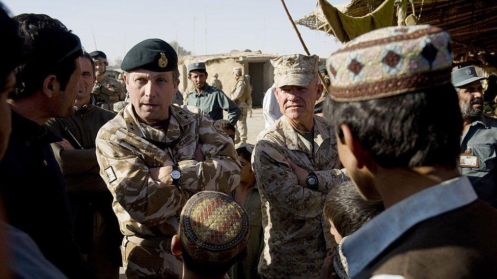 El general británico Nick Carter (con la boina) y el brigadier general estadounidense Larry Nicholson conversan con afganos, noviembre de 2009