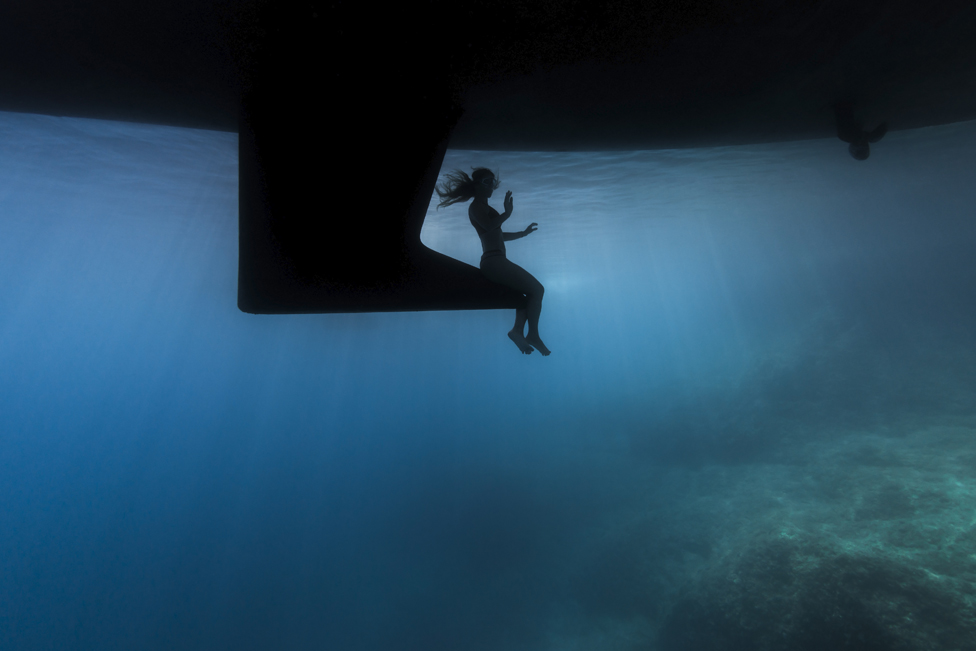 A silhouette of a woman surrounded by the blue background of the sea.