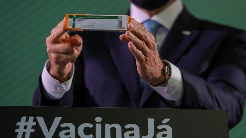 De máscara, João Doria mostra embalagem da Coronavac, com palanque em baixo exibindo a palavra #VacinaJá