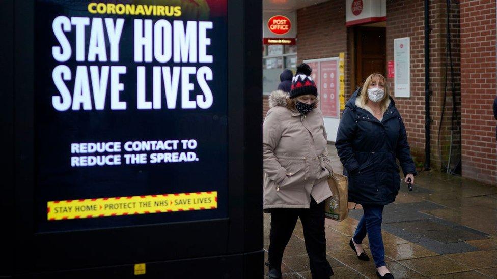 Duas mulheres passam por uma placa que pede para população ficar em casa em Hyde, Grande Manchester, no Reino Unido