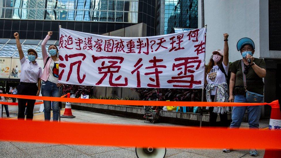 """部份被告的家屬不滿法庭的決定,在法庭大樓外拉起寫著""""被迫守護家園被重判?天理何在""""的橫幅。"""
